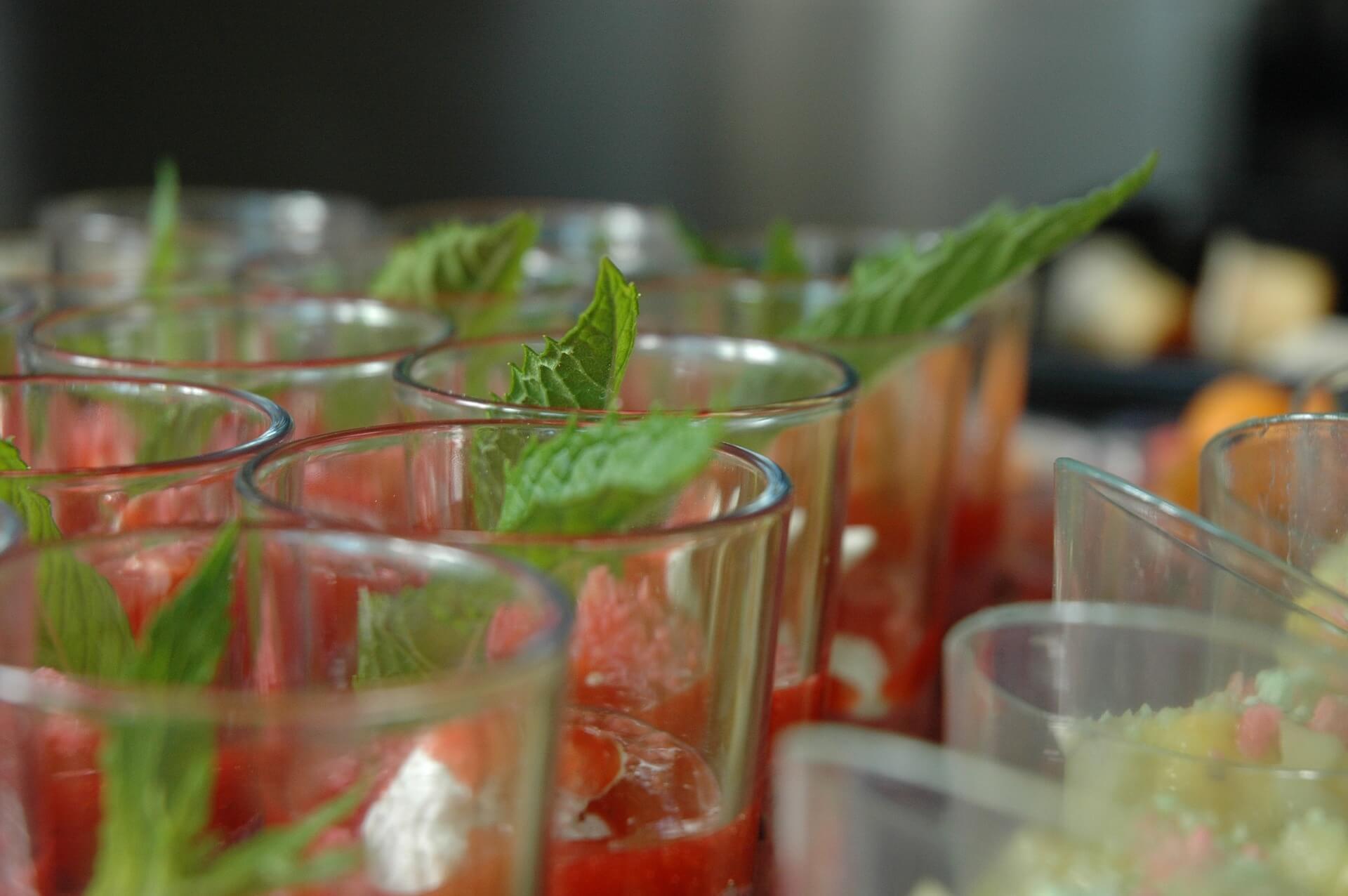 Présentation de quelques verrines de bar et Truite Fumée, avec une feuille de menthe déposée dans chaque verrine.