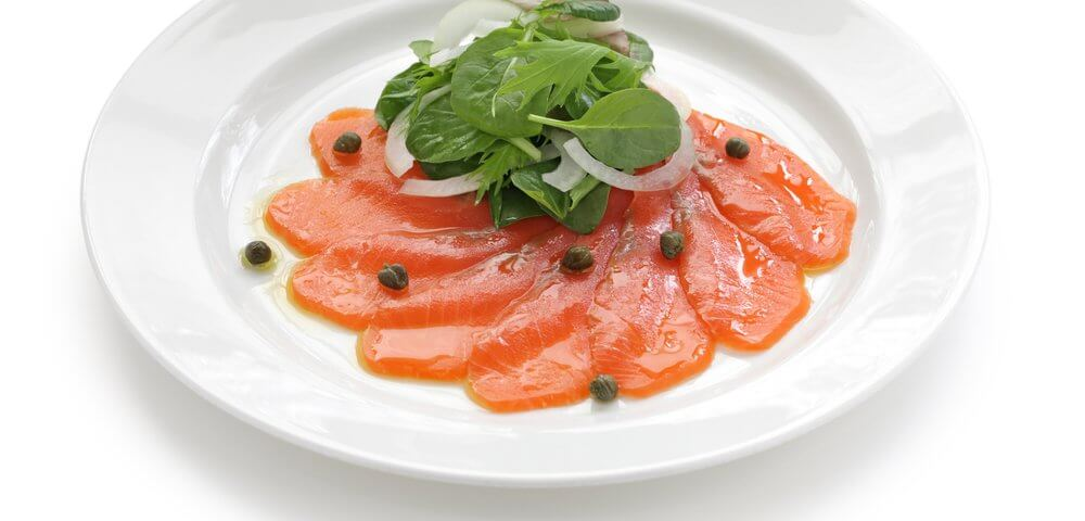 Carpaccio de saumon, présenté sous forme de coulis dans une assiette blanche, avec quelques feuilles de salade dessus.