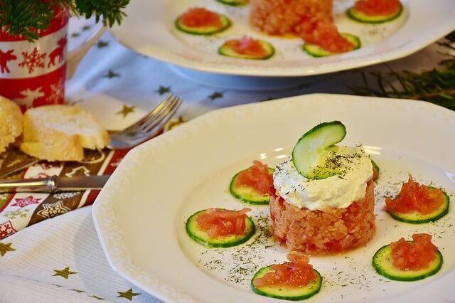 Tartare de saumon avec une cuillère de crème fraiche sur le dessus et des rondelles de courgette.