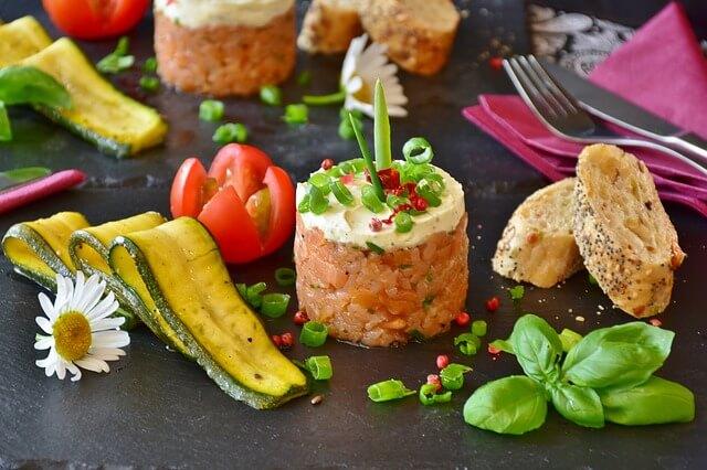 Tartare de Saumon à l'oseille sur une ardoise, entouré de légumes et de feuilles de basilic.