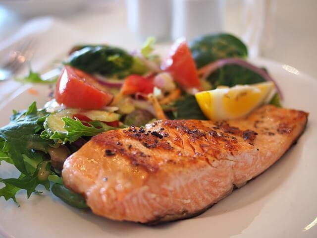 Pavés de saumon accompagné de légumes et de jus de citron.