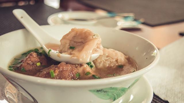Dans une assiette creuse repose un Agneau aux Cardons Lyonnais avec sa sauce.