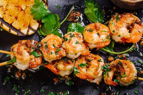 5 crevettes misent en brochette sur une planche en ardoise.