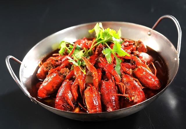Dans un plat en inox, une dixaine de crevettes sont diposées de manière circulaire et flambée au cognac.