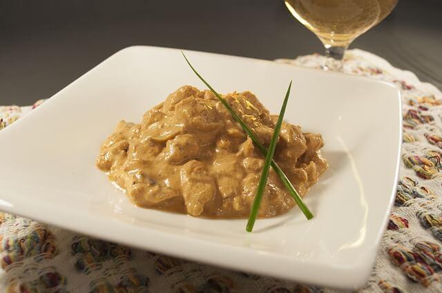 recette de boeuf stroganoff, originaire de russie. Présentation dans une assiette et deux brins de ciboulette.