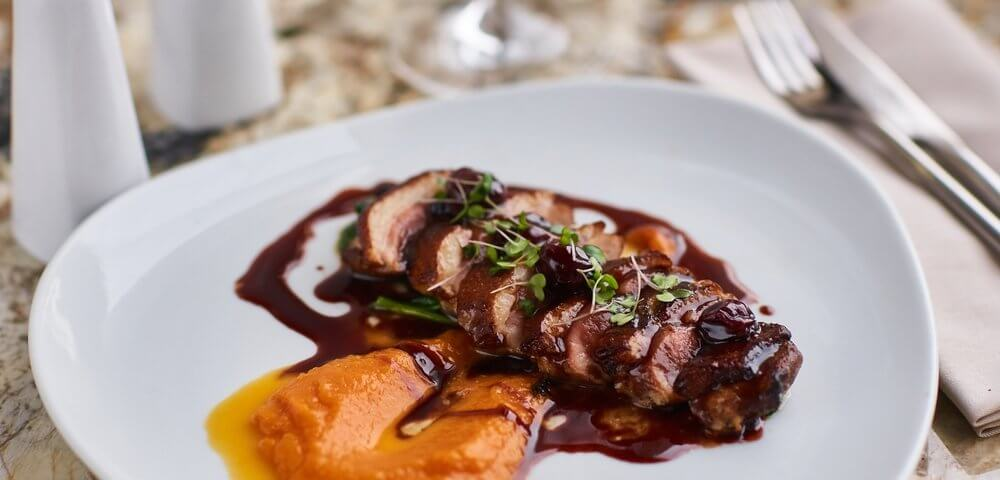 Magret de canard sur un lit de pruneaux et abricots. Sur la photo la viande est accompagnée par une purée de potiron.